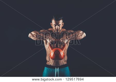 Fitness man doing a weight training by lifting a heavy kettlebell.