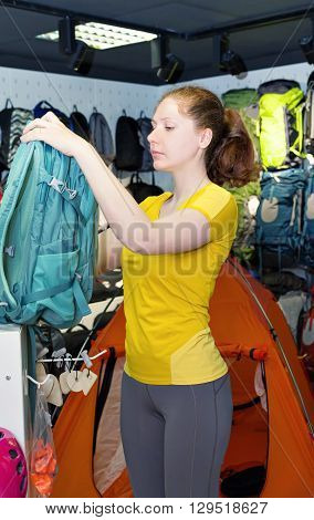 Young caucasian girl in the yellow shirt is considering travel backpack in the store. Specialized products for tourism and mountaineering. The buyer on background of a display of tents and backpacks