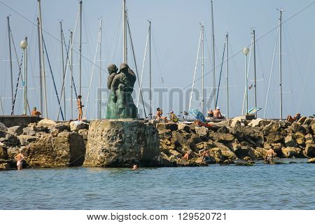 Viareggio Italy - June 28 2015: People resting near the monument to the sailors family by Inaco Biancalana. Viareggio is the famous resort on the coast of the Ligurian Sea