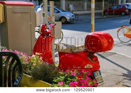 Viareggio Italy - June 28 2015: Red moped parking near decorative box with flowers. Province Lucca Tuscany region of Italy