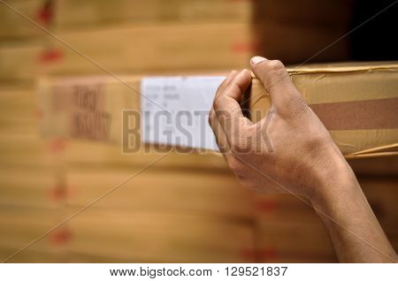 Man Loading Products for Delivery. Delivery boy loading goods in a truck for delivery. The hand is in sharp focus but the face is not in the image.