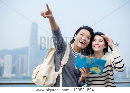 Two woman tourists pointing out the location