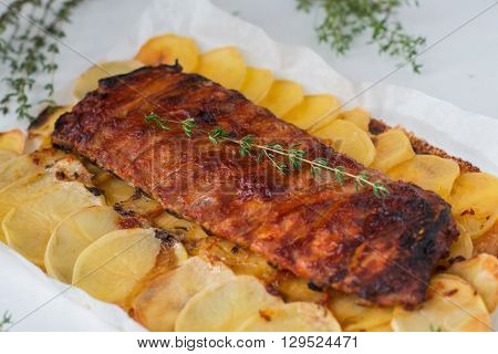 freshly cooked juicy pork ribs with potatoes on white background