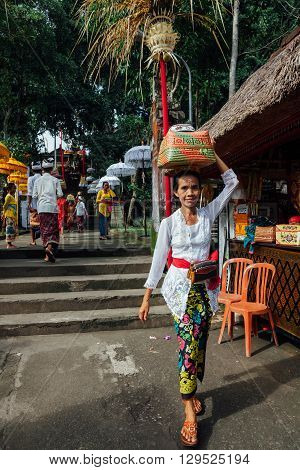 UBUD, INDONESIA - MARCH 02: Balinese woman in traditional clothes carrying ceremonial box with offerings on her head during Balinese New Year or Nyepi Day celebrations on March 03 2016 in Ubud Bali.
