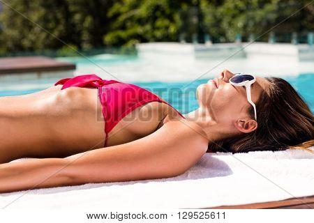 Woman enjoying sunbath on the pool edge on a sunny day