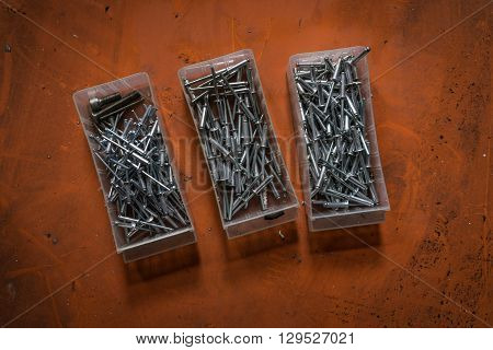 A shot of rivets or mechanical fasteners over an orange background.