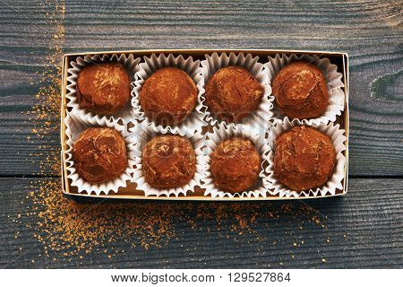 Homemade chocolate truffles on wooden background