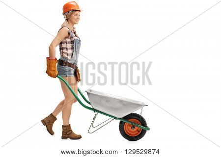 Female construction worker pushing an empty wheelbarrow isolated on white background