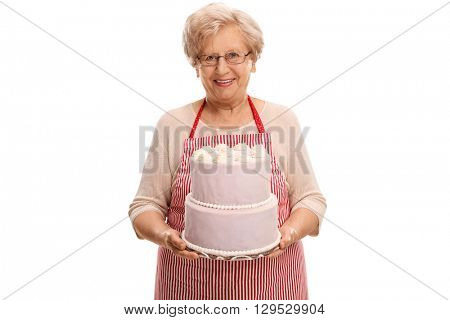 Studio shot of a mature lady holding a cake and looking at the camera isolated on white background