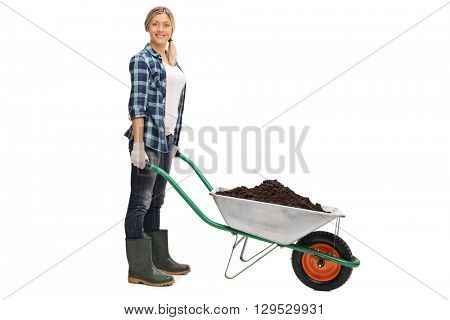 Young woman posing with a wheelbarrow full of dirt isolated on white background