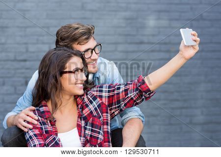 Young couple in spectacles taking a selfie on a mobile phone