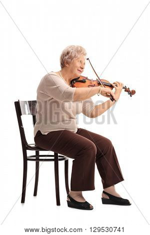 Vertical shot of an elderly lady playing a violin seated on a chair isolated on white background