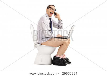 Excited businessman working on laptop and talking on phone seated on a toilet isolated on white background