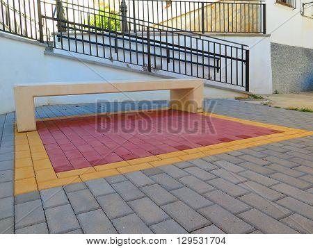 White concrete bench on colourful pavement in Alora Village Andalucia