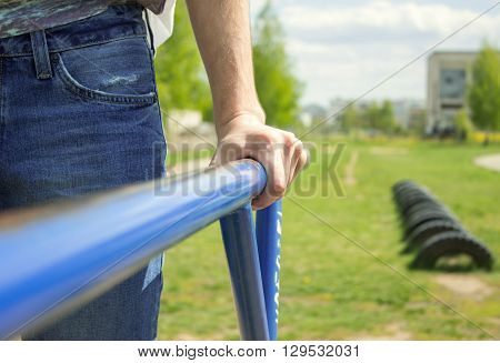 Young Man Doing Triceps Dip On Parallel Bars Outdoors