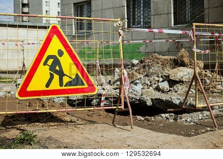 Road signs in a street under reconstruction symbol. Road construction site with signs