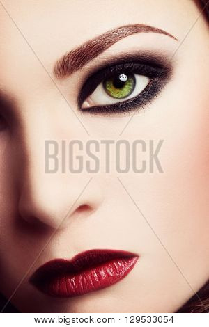 Vintage style close-up shot of woman face with smokey eye makeup and red lips