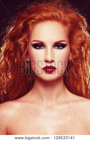 Portrait of young beautiful sexy woman with long curly red hair and stylish smokey eye make-up