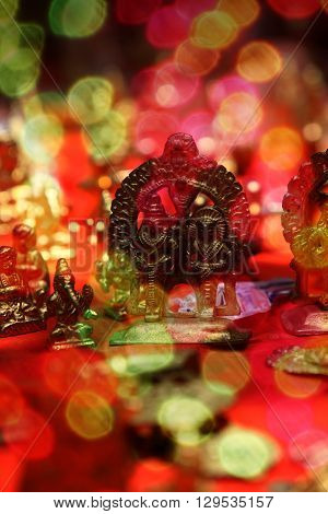Brass idols of hindu gods during festival behind blur colorful lights.
