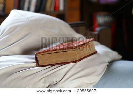 Old book in red velvet cover laid on a pillow in a bedroom shallow depth of field shot