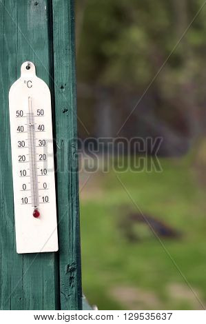 Temperature gauge on a green wooden wall garden in the blurred background vertical outdoor shot