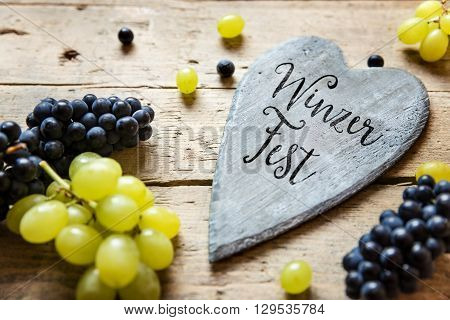 Blue and white grapes and a wooden heart with german word Winzerfest on it which means wine festival