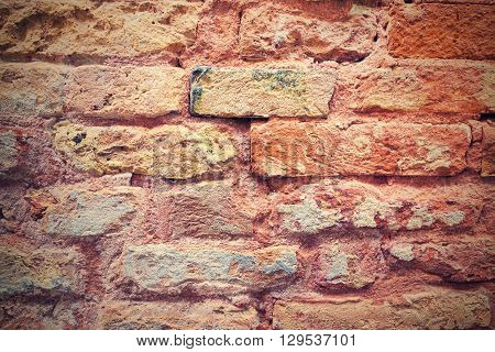 the old textured surface of a red brick wall for wallpaper and for a background in retro style