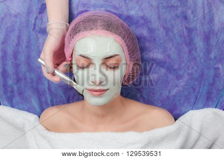 Close-up portrait of beautiful girl applying facial clay mask and beauty treatments lying on a table in spa beauty salon. Cosmetician applying facial beauty mask for young beautiful woman at spa salon