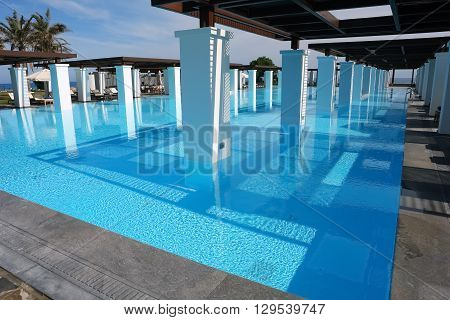 HERAKLION, CRETE, GREEC, - MAY 13 2014: The blue swimming-pool modern building with columns and beach in popular luxury class hotel on the Mediterranean coast of Crete, May 13, 2014, Greece.