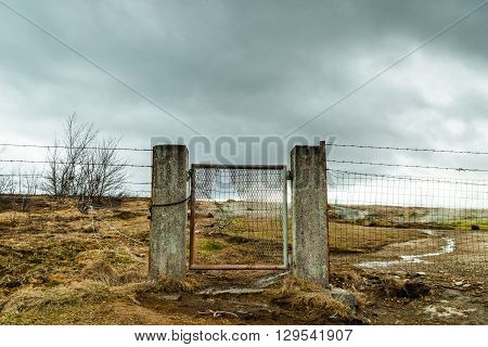 Broken Gate On A Field With Barb Wire