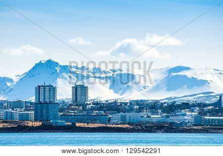 Reykjavik city in Ieland beneath a mountain with snow