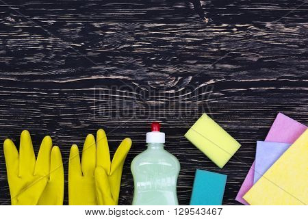 Detergent, sponges, rags and latex gloves on wooden background