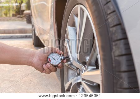 Man Holding Pressure Gauge And Checking Air Pressure Of The Car