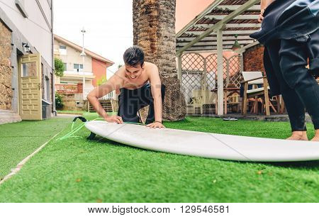 Portrait of surfer man with wetsuit waxing surfboard of a beautiful woman. Summer sports concept.