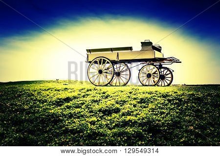 Vintage photo of beautiful wagon in beautiful nature scene farmland.