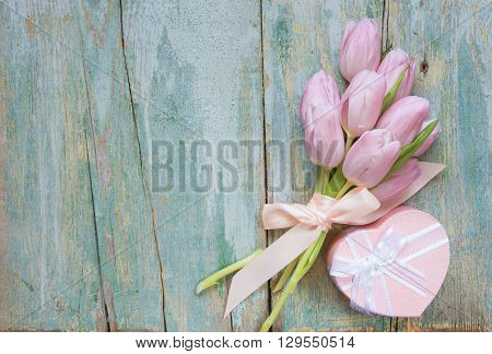 Bouquet of pink tulips tied with a satin ribbon and gift box in the shape of a heart with a bow on the old blue wooden background with space for text