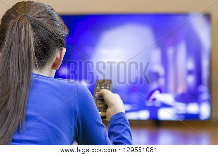 Teenager girl with remote control laying down and watching tv on cartoons.