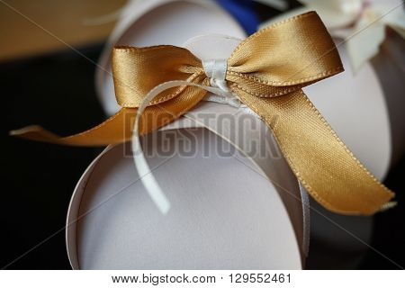 Small papery gift box with a golden ribbon on the top