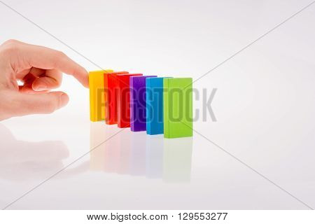 Finger in touch with multi color domino on white background