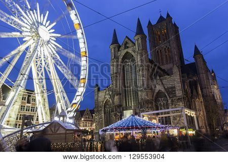 Saint Nicholas' Churchl in Ghent in Belgium with a ferris wheel in the foreground