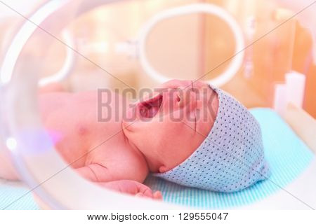 Newborn Baby Yawning While Lying In Infant Incubator