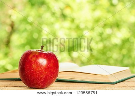 Apple and opened book on the wooden table on green background