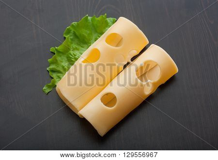 Top view of two rolled pieces of maasdam cheese and green lettuce on the black wooden table