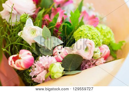 gardening, floristry, sale, holidays and flora concept - close up of bunch in paper at flower shop