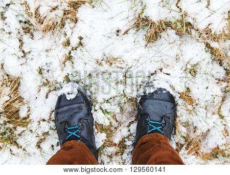 Two male legs with hikking boots standing on snowed wet grass