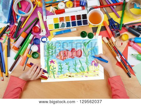 red fish underwater, crab on seabed, child drawing, top view hands with pencil painting picture on paper, artwork workplace