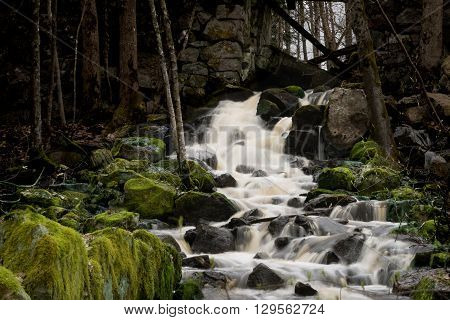 Small waterfall with green moss on rocks. water running through old stonewall