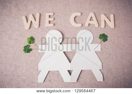 paper dolls holding hands with green leaves and 'WE CAN' word