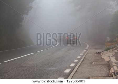 Turn of the road and the car in a foggy cloudy day in rural area.