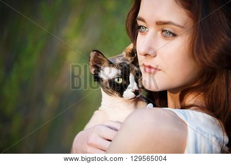 Portrait of the attractive girl with sphynx